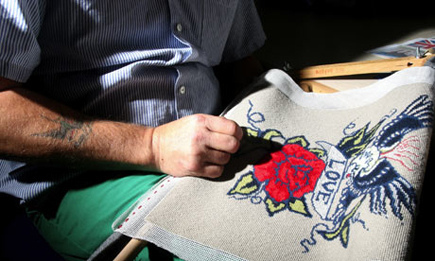 Prisoner embroidering a cushion from jail